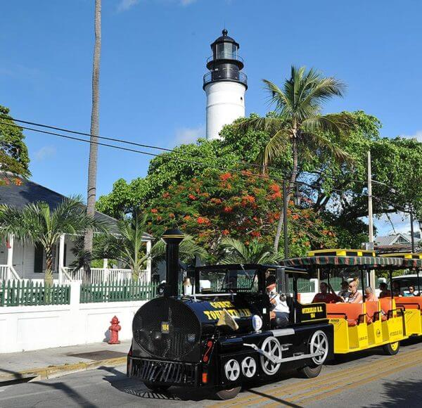 conch tour train driving past key west lighthouse