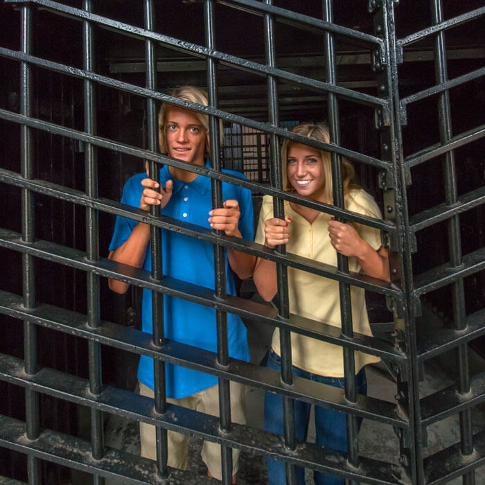 two guests standing behind bars inside a cell at the Old Jail Museum in St. Augustine, FL