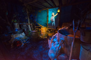museum display showing a moonshiner camp at night with barrels, bottles and a fireplace and a hologram of a moonshiner in the background