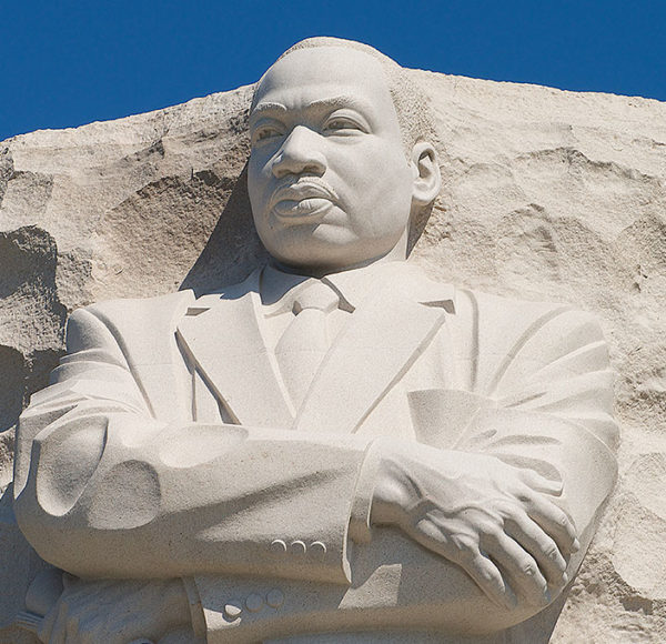 Picture of top of Martin Luther King Jr. Memorial showing the top half of Martin Luther King standing with arms crossed and carved out of a large stone