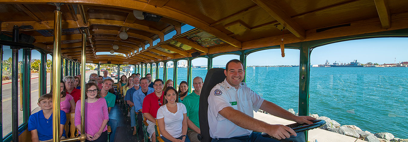 interior picture of a san diego old town trolley showing guests and conductor seated with windows showing view of the ocean