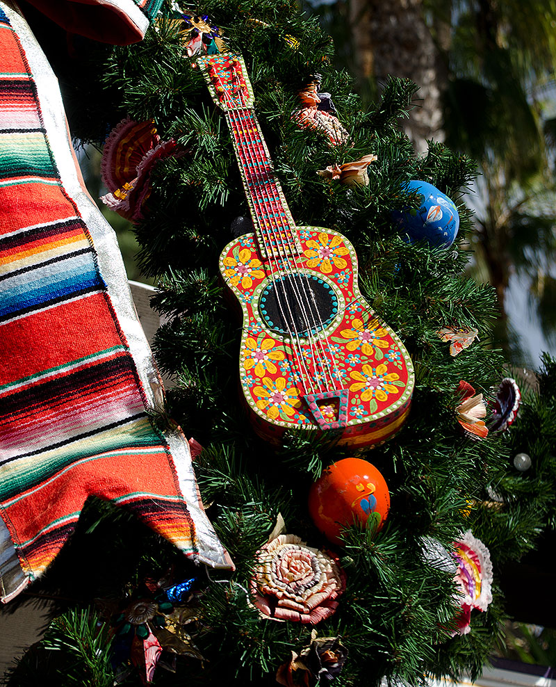 close up picture of a christmas tree featuring ornaments, a mexican-themed guitar and a mexican-themed piece of fabric