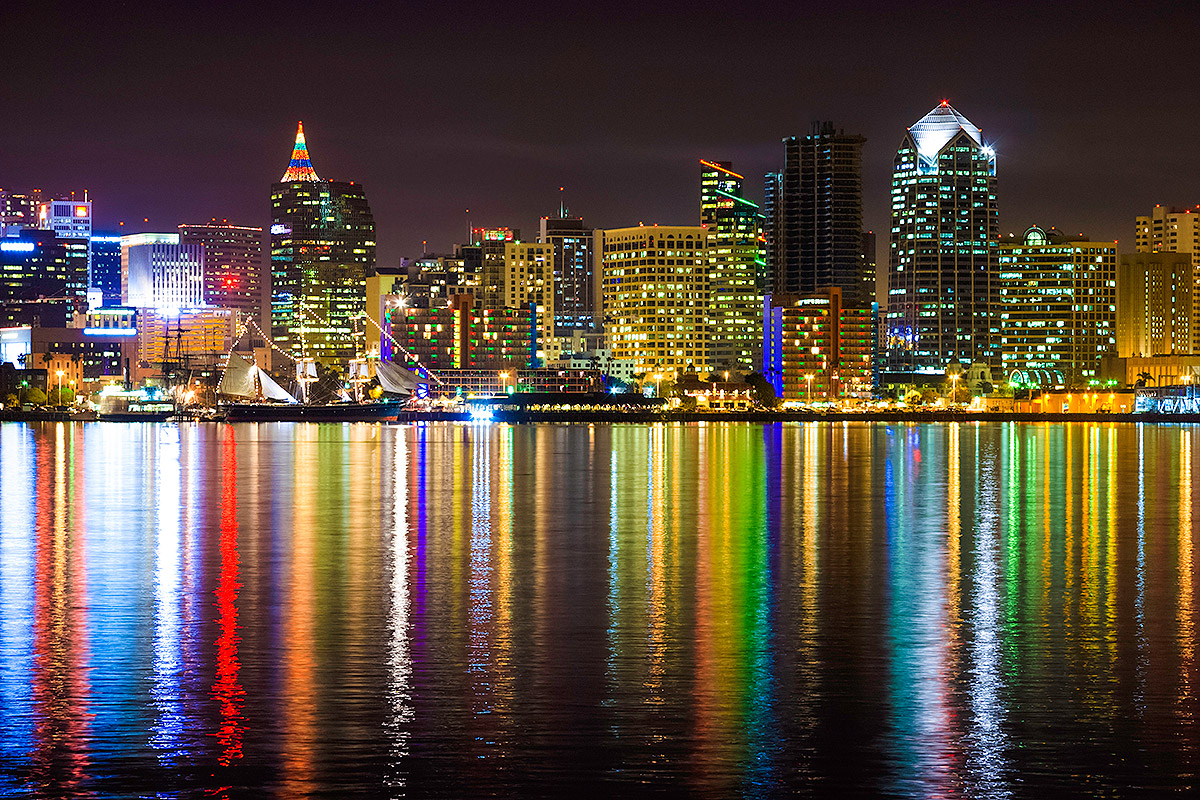 night time picture of San Diego skyline with lights from buildings reflecting on the water