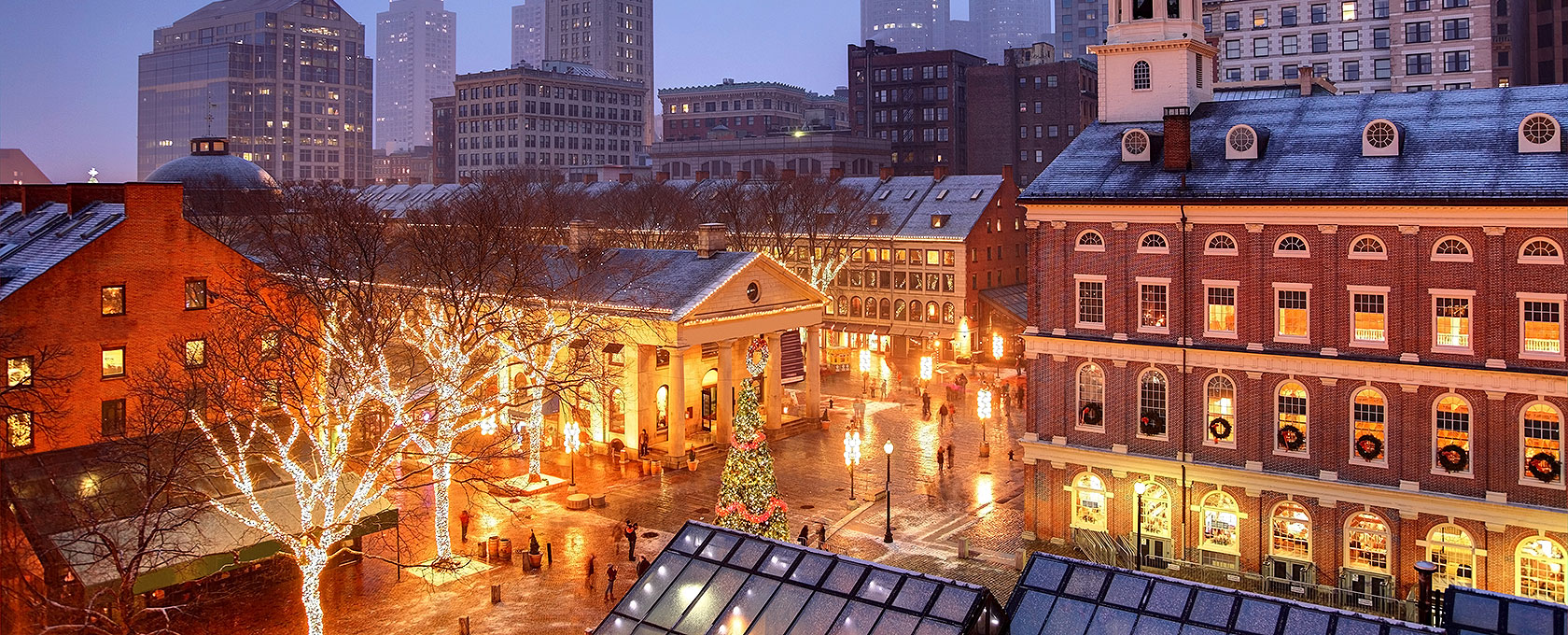Nighttime picture of Faneuil Hall in Boston during Christmas with various trees decorated in holiday lights
