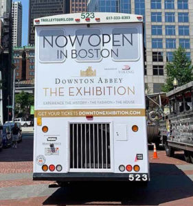 boston trolley showing an advertisement covering the entire back with the words 'Now Open In Boston Downtown Abbey Exhibition'