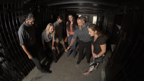 guests and tour guides standing around inside a cell at the St. Augustine Old Jail and they're all looking at an EMF meter held by one of the guides