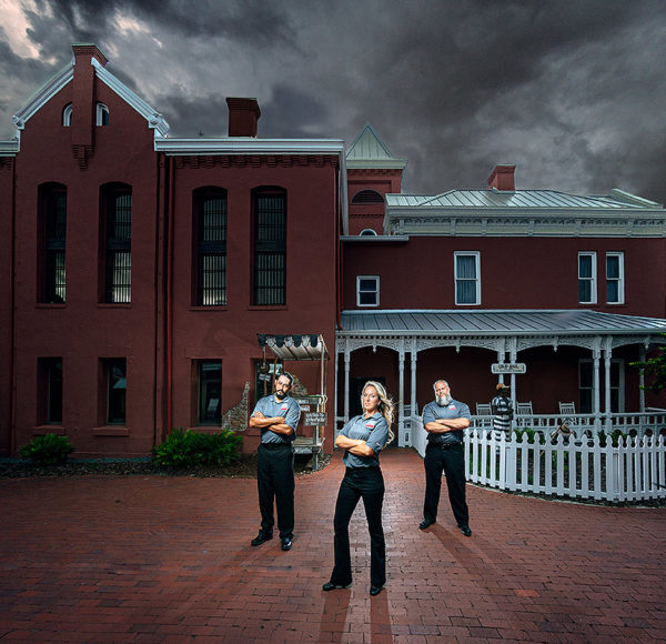 three tour guides standing in front of St. Augustine Old Jail