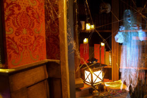 indoor picture of a spooky looking room with a library, table, lantern, spider webs and a ghost
