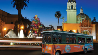 San Diego trolley driving at night past Balboa Park with a fountain, historical building and Christmas tree behind it